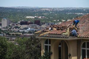 three men replacing a roof in colorado