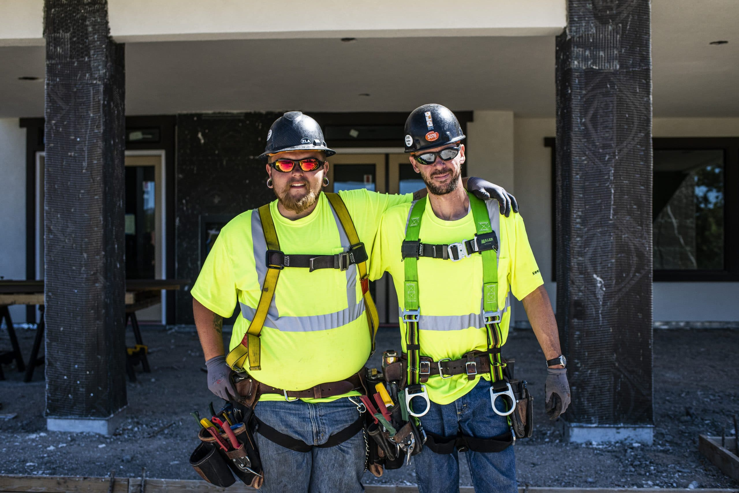 Two roofing employees standing together