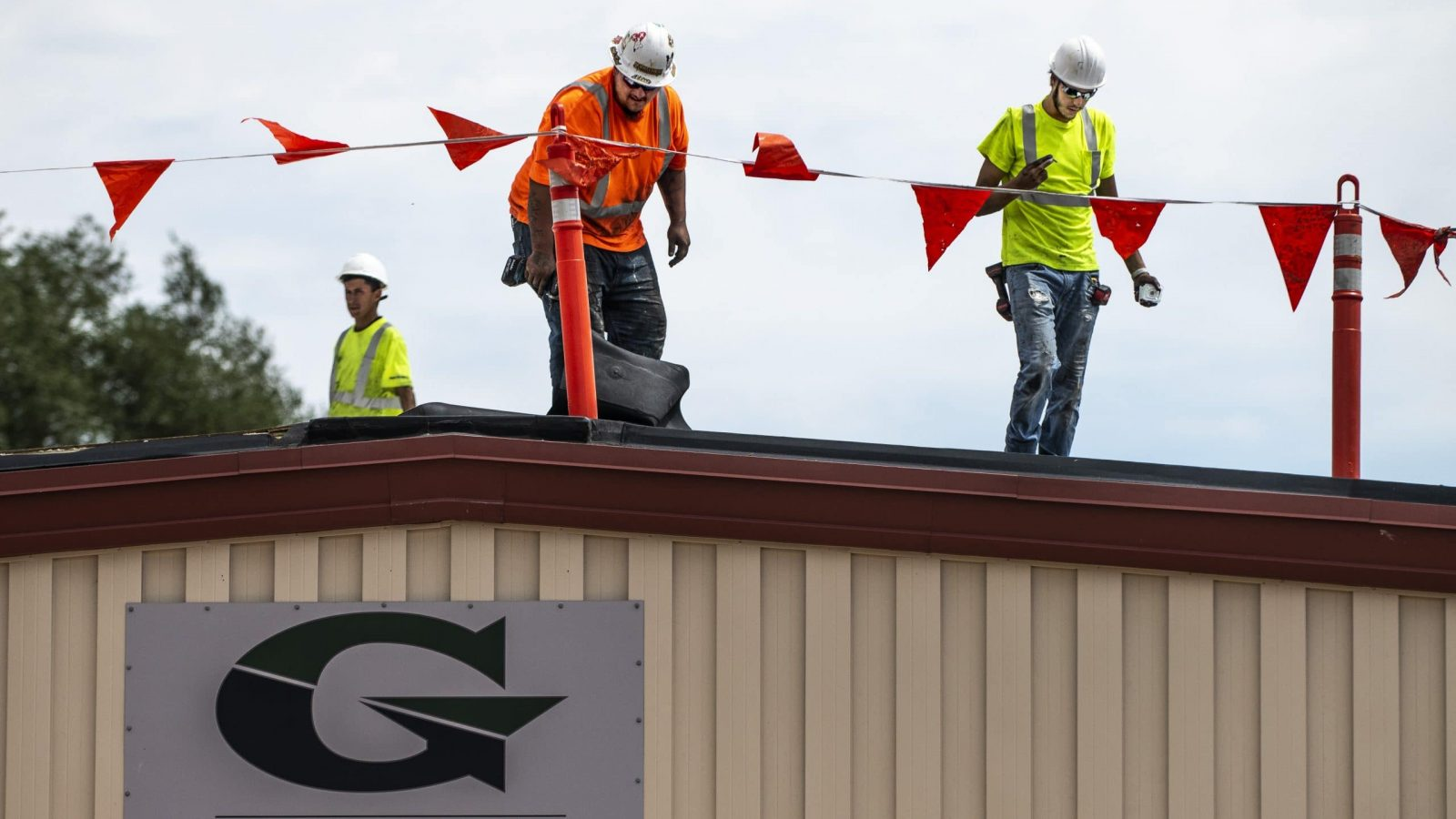 three men working on the Goal High School roof