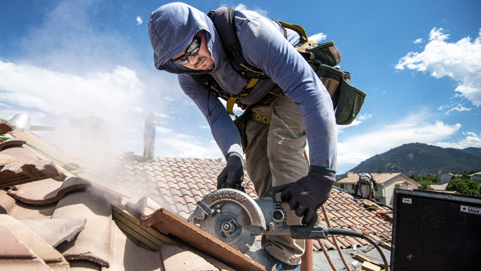 Man cutting tile for roof replacement