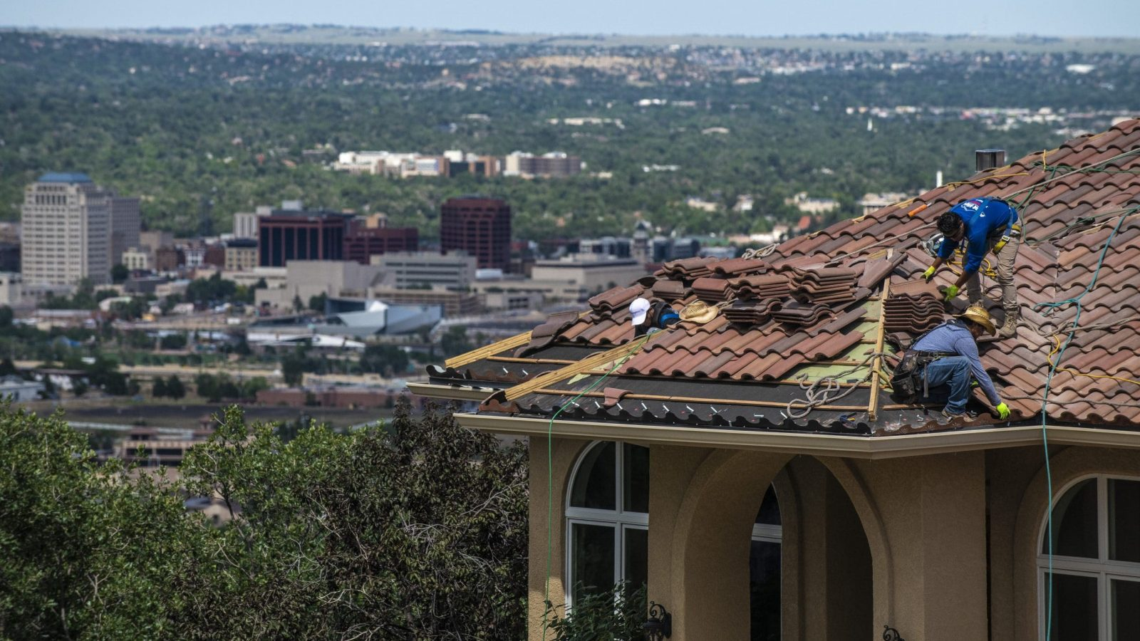 three men replacing a roof in colorado